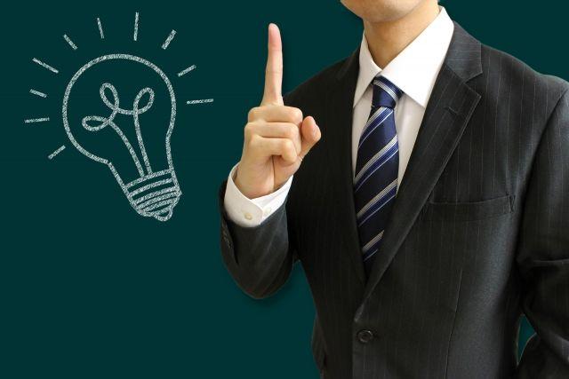 チョークで描かれた豆電球と並んだビジネスマン